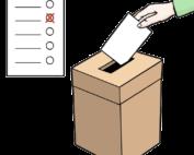 Eine Hand steckt einen Zettel in einen Kasten.