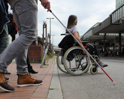 Frau mit Rollstuhl und Person mit Langstock überqueren Straße