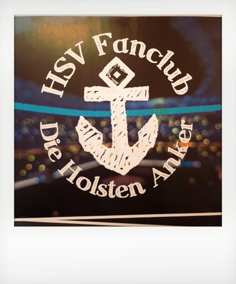 Foto: vorläufiges Logo HSV Fanclub. Mittig Anker, darum herum Schriftzug: HSV Fanclub Die Holsten Anker. Im Hintergrund Stadion
