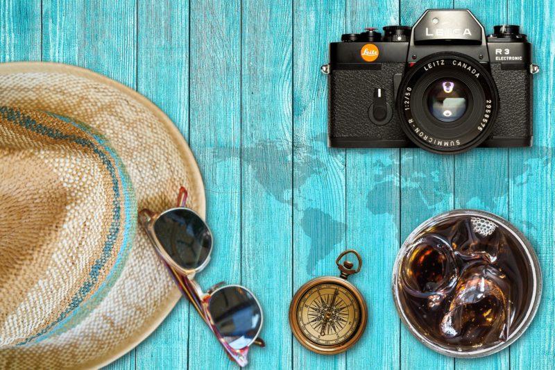 Foto: Auf Tisch liegen Kamera, Sonnenbrille, Strohhut, Kompass, Getränk mit Eiswürfeln