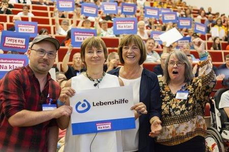 Ulla Schmidt und weitere Personen halten ein Lebenshilfe-Schild hoch
