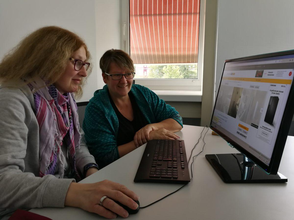 Zwei Frauen sitzen vor einem Computermputer