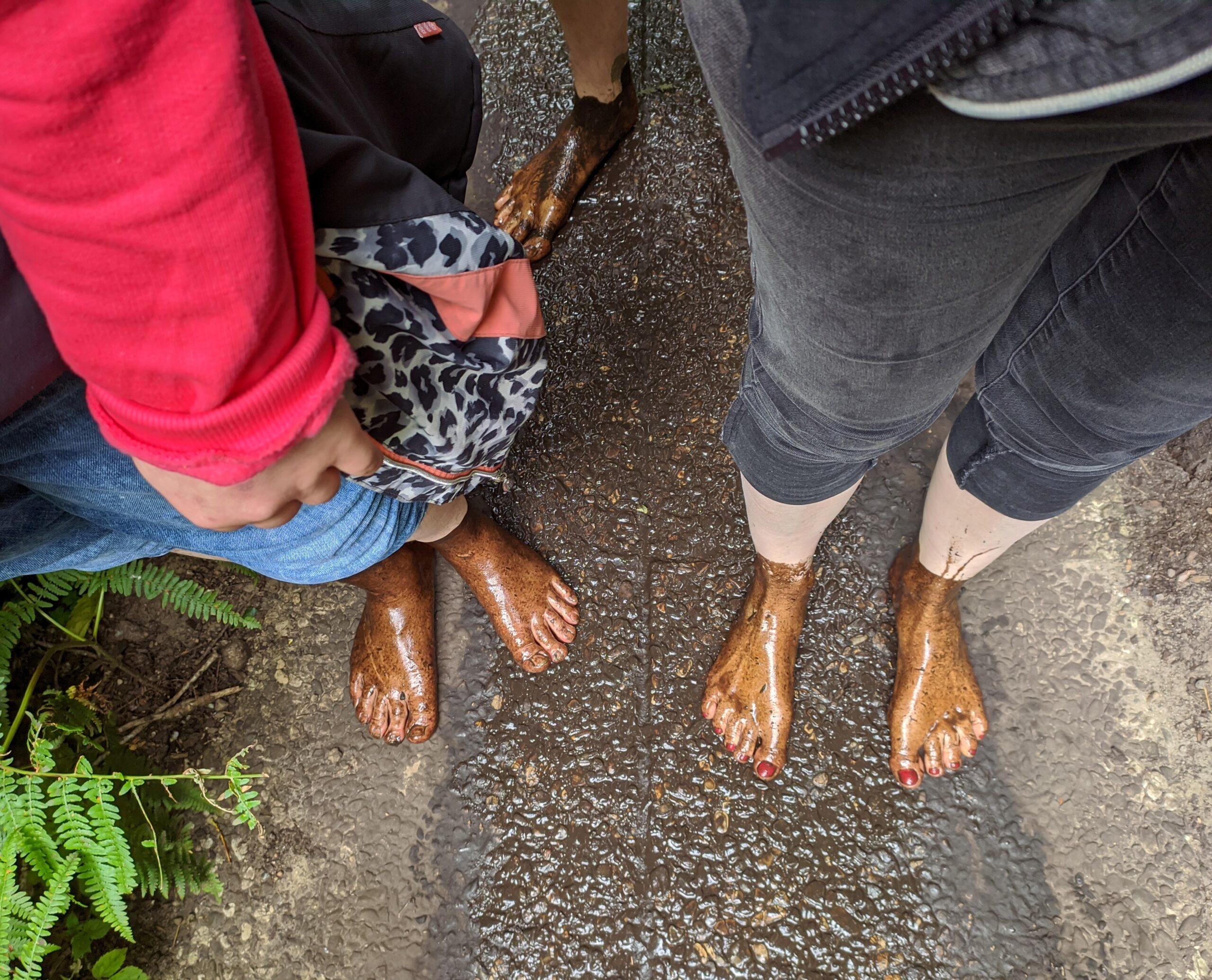 Nackte Füße mit Schlamm bedeckt
