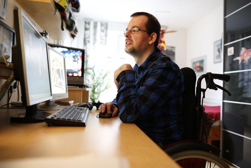 Mann sitzt am Schreibtisch und guckt auf PC Bildschirm