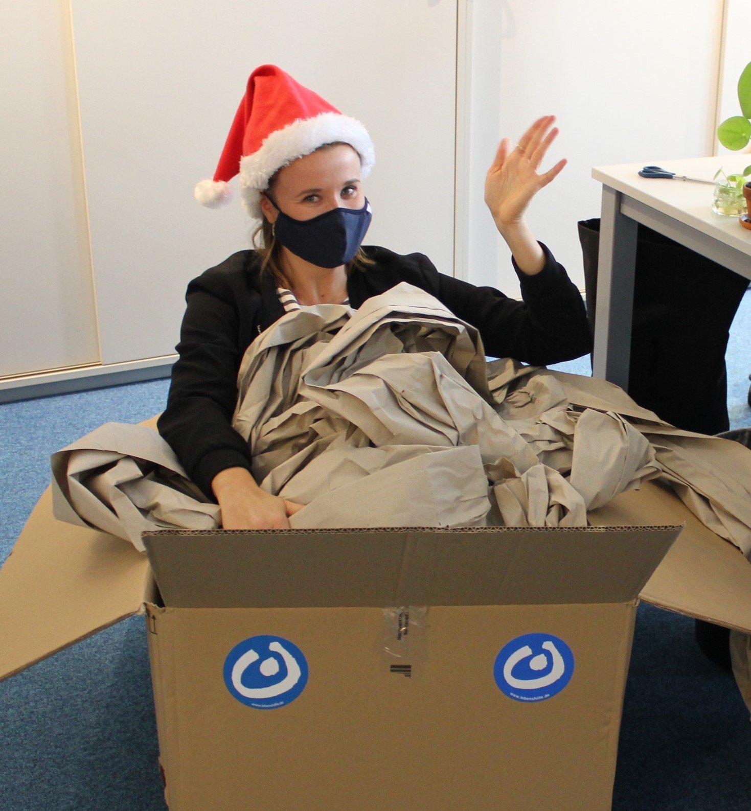 Frau mit Weihnachtsmütze sitzt im Karton, mit Lebenshilfe-Aufklebern