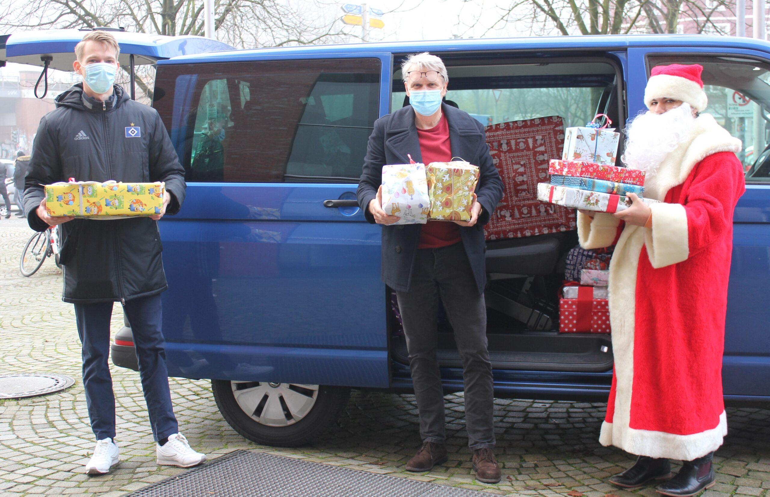 Zwei Männer und ein Weihnachtsmann mit Geschenken