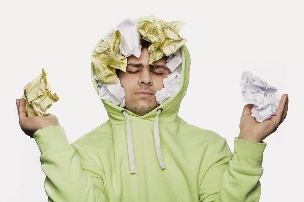 Mann mit mit Kapuzenpullover. In der Kapuze sind viele zerknüllte Zettel