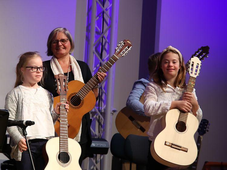Mächen mit Down-Syndrom halten Gitarren + Lehrerin mit Gitarre