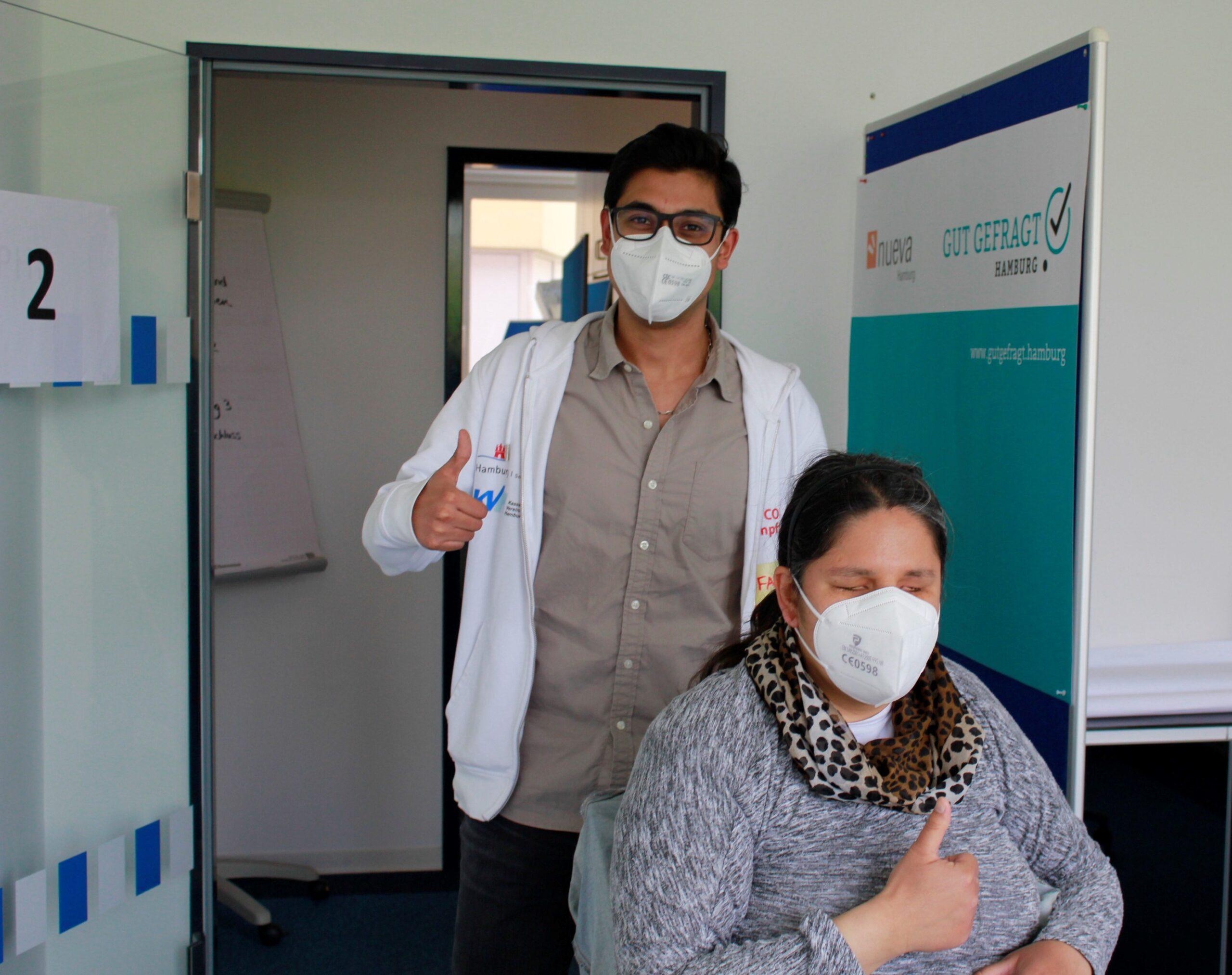 Arzt und blinde Patientin mit Maskenstrecken den Daumen hoch