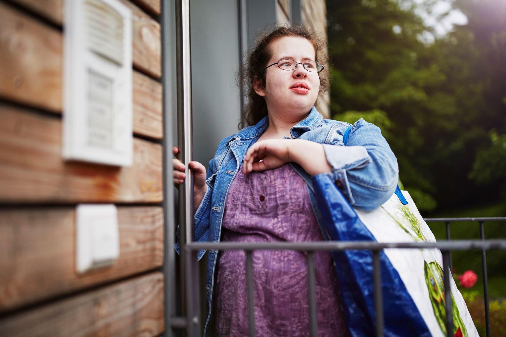 Foto: Junge Frau mit Einkaufstasche über der Schulter steht vor Wohnungstür