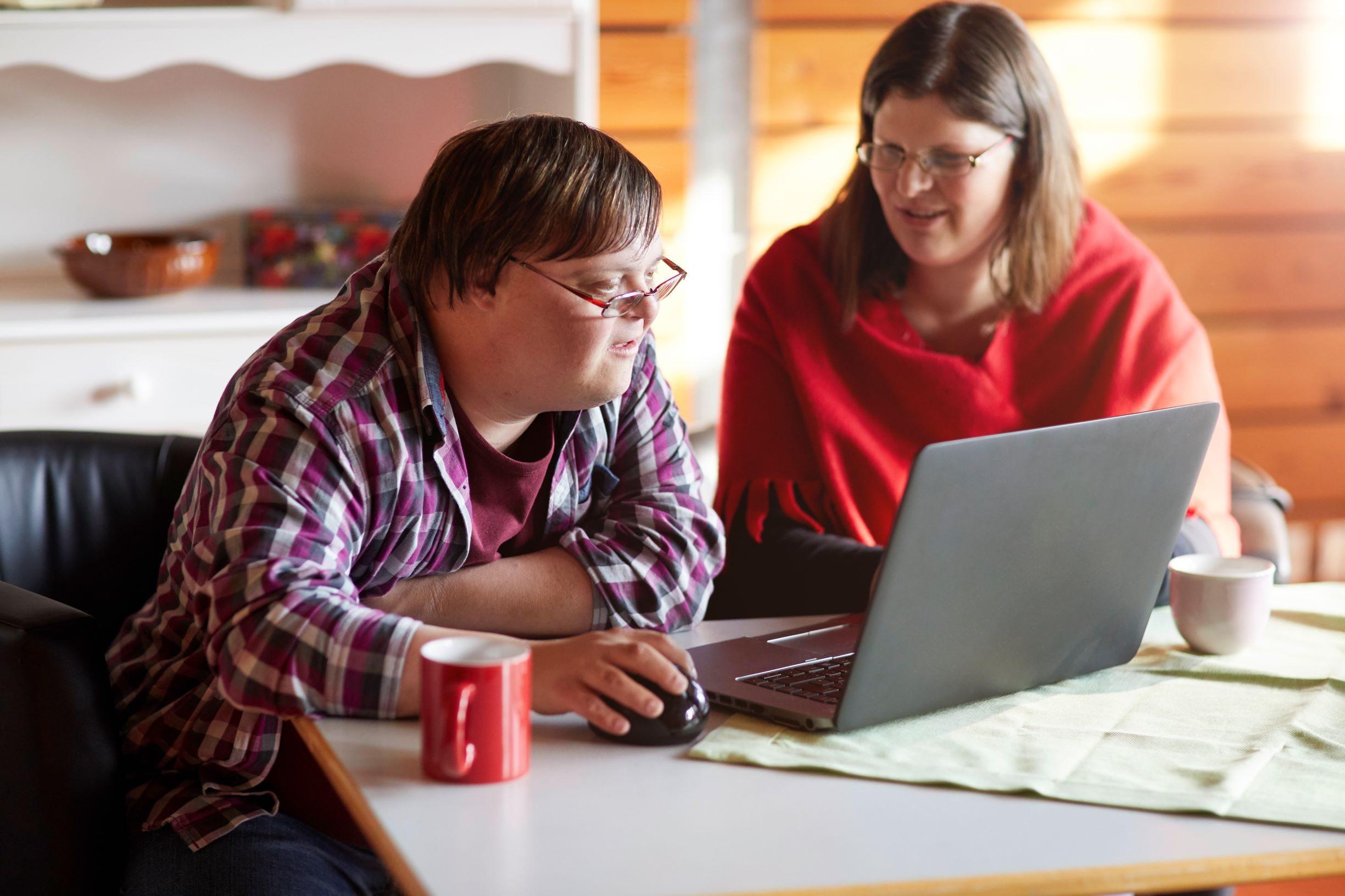 Foto: Mann sitzt an Tisch vor einem geöffneten Laptop, neben ihm sitzt eine Frau