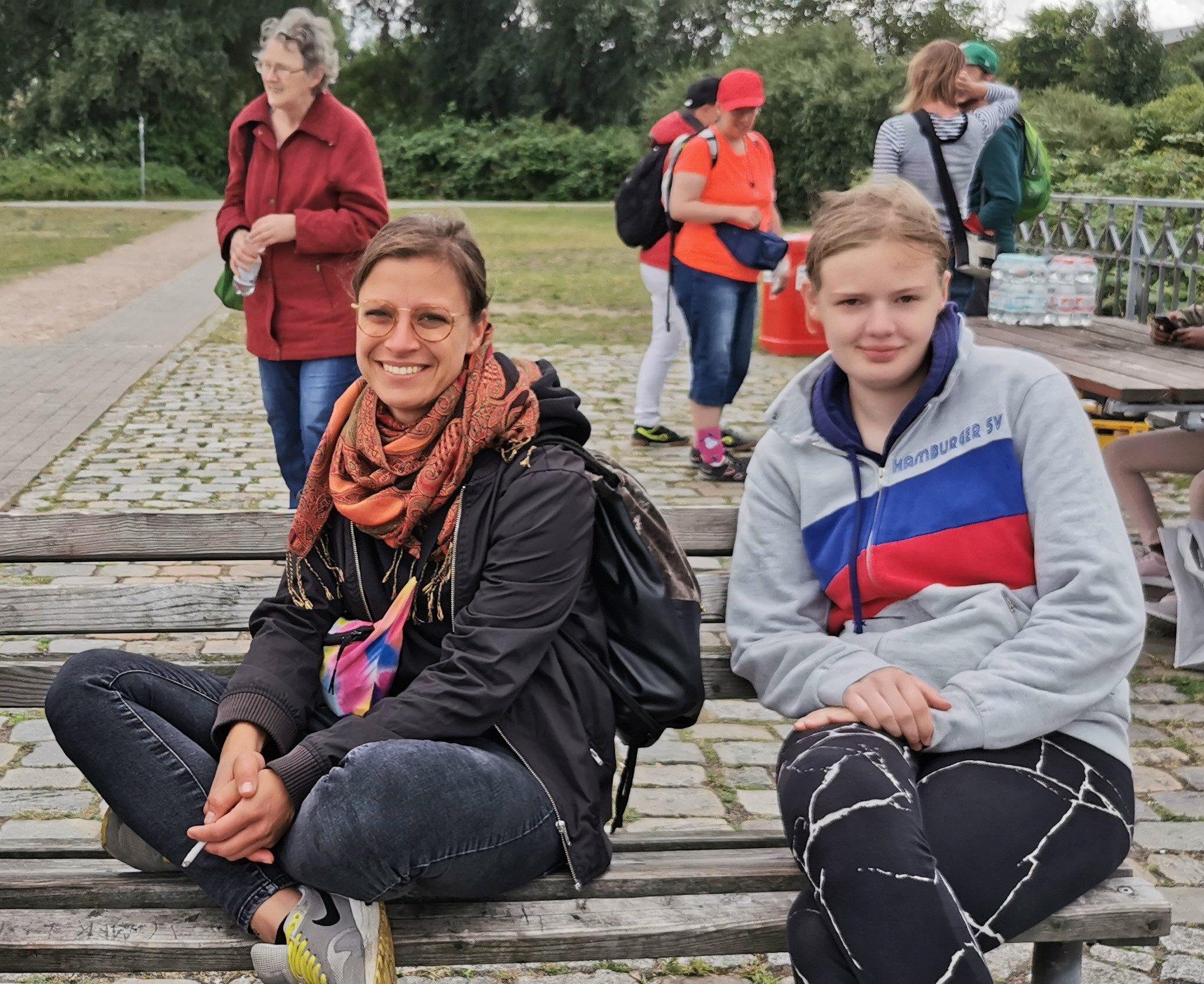 Zwei junge Frauen sitzen auf einer Bank, im Hintergrund andere Menschen.