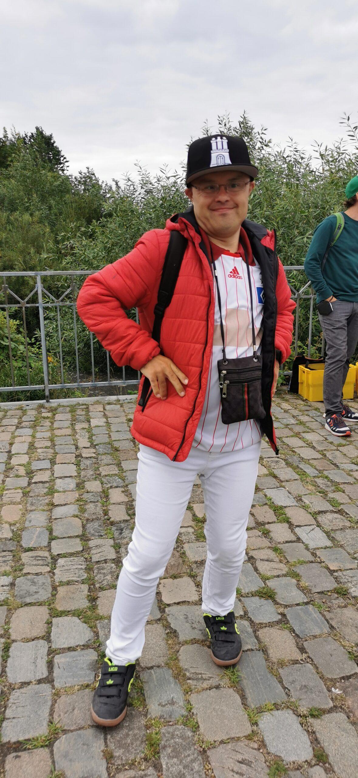 Junger Mann mit Down-Syndrom grinst, trägt Käppi mit Hammaburg und Brustbeutel.
