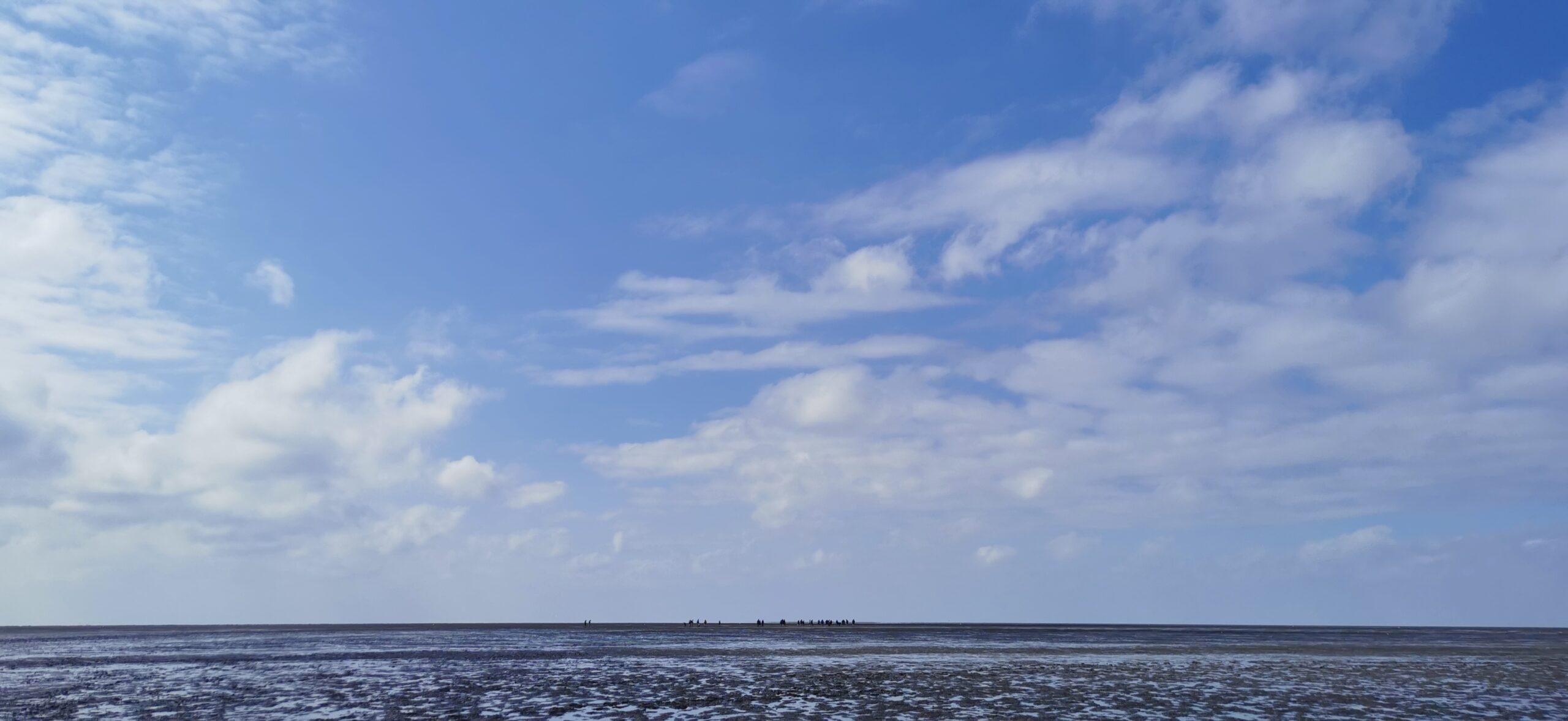 Weiter Blick über das Watt, blauer Himmel mit Wolken