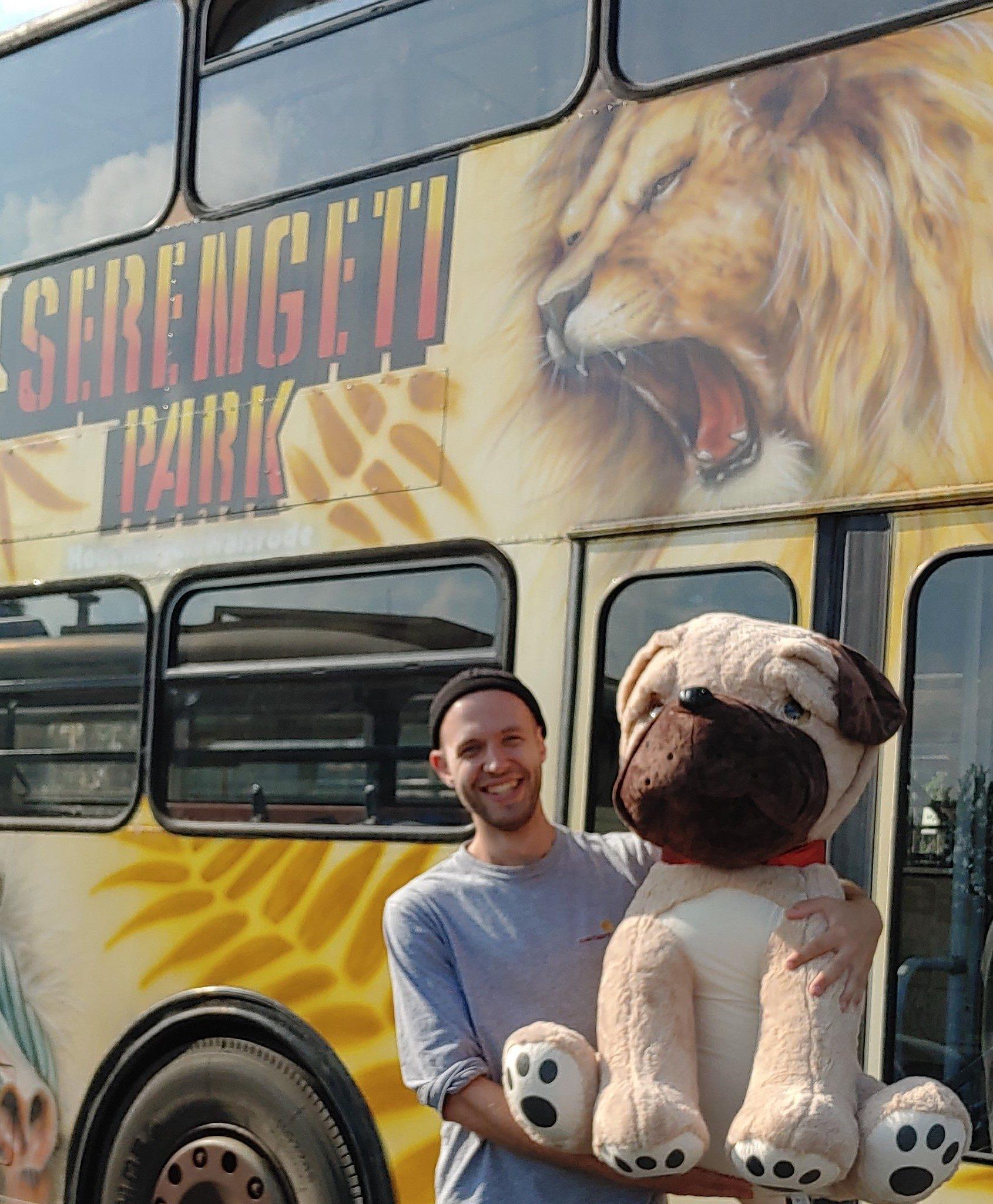 Junger Mann steht vor Doppeldeckerbus mit Aufschrift Serengeti Park, hält einen sehr großen Hund aus Plüsch im Arm.