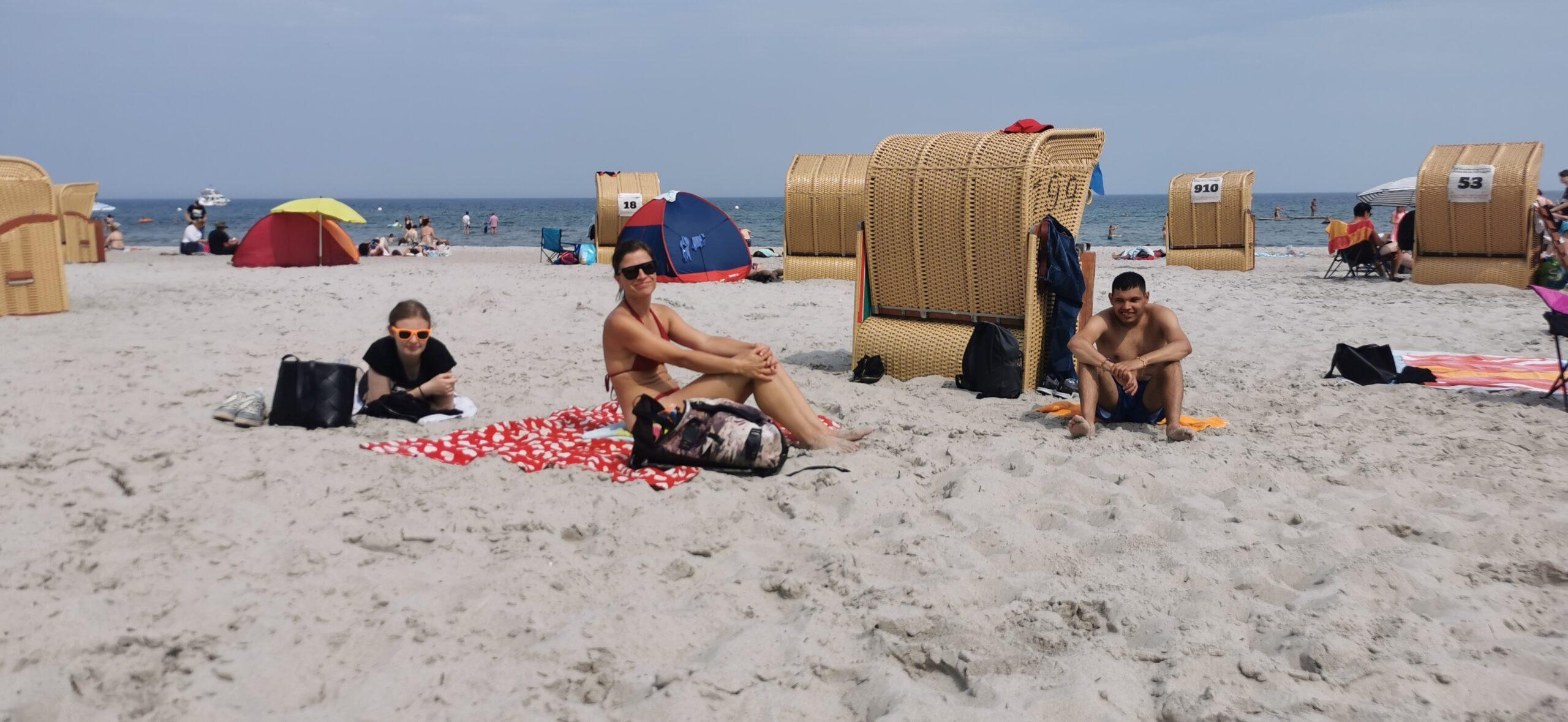 Drei Menschen sitzen am Strand vor Strandkörben.
