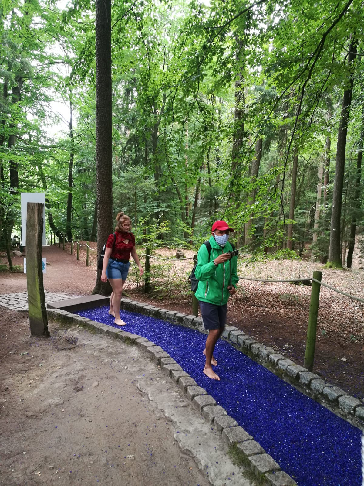 Im Wald: Zwei junge Menschen gehen über blaue Glasscherben.