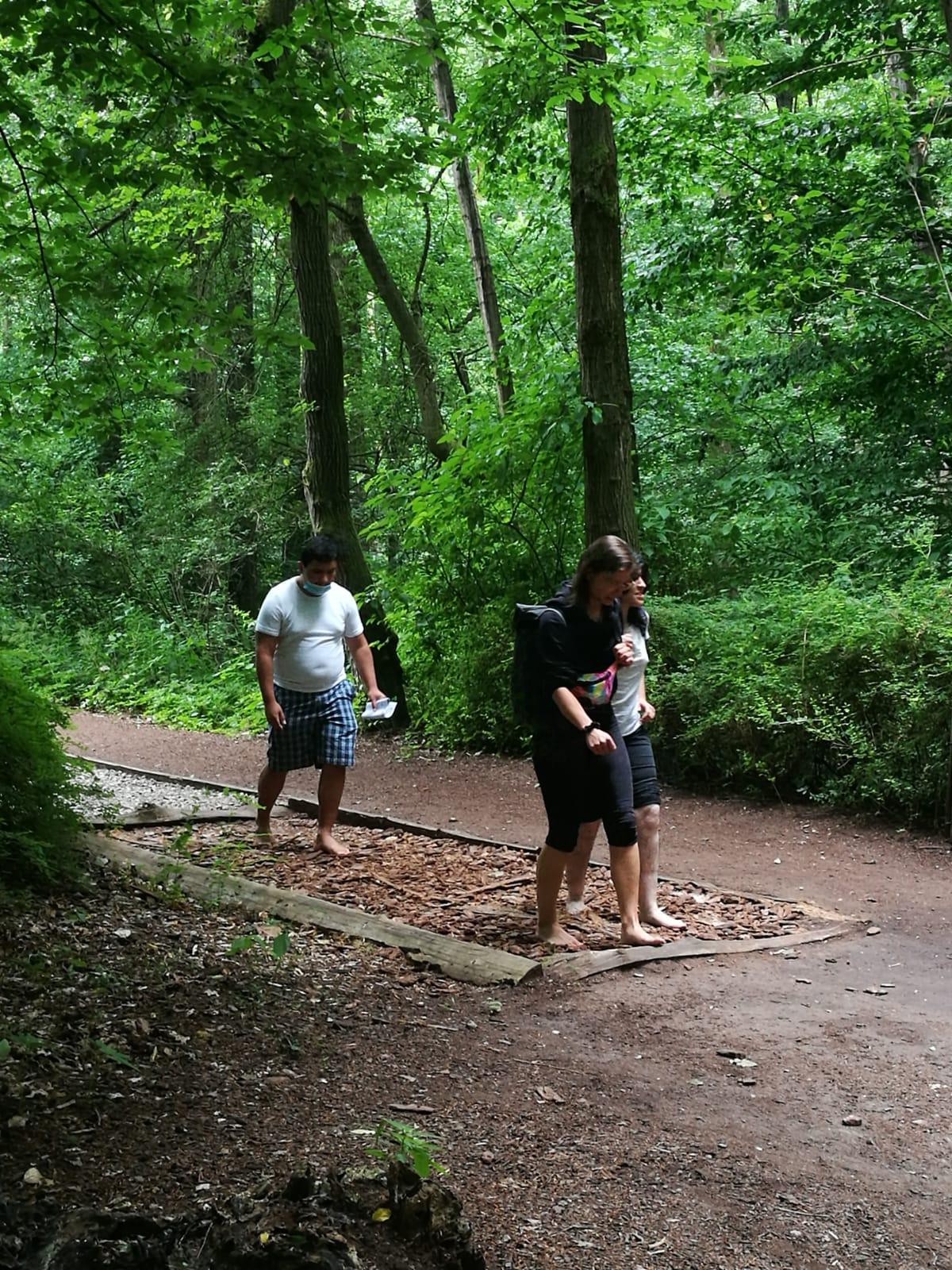 Im Wald: Zwei junge Menschen gehen barfuß über kleine Holzstücke.