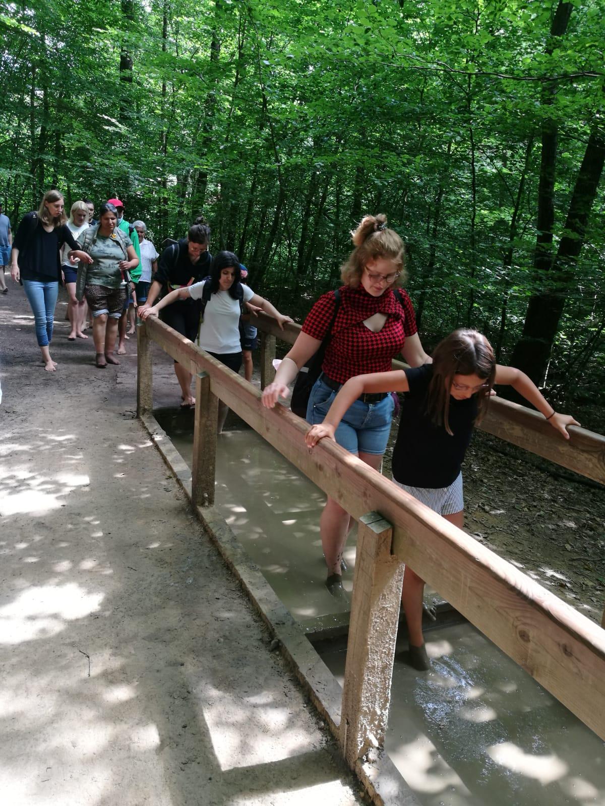 Junge Menschen gehen barfuß durch den Matsch, halten sich an einem Holzgeländer fest.
