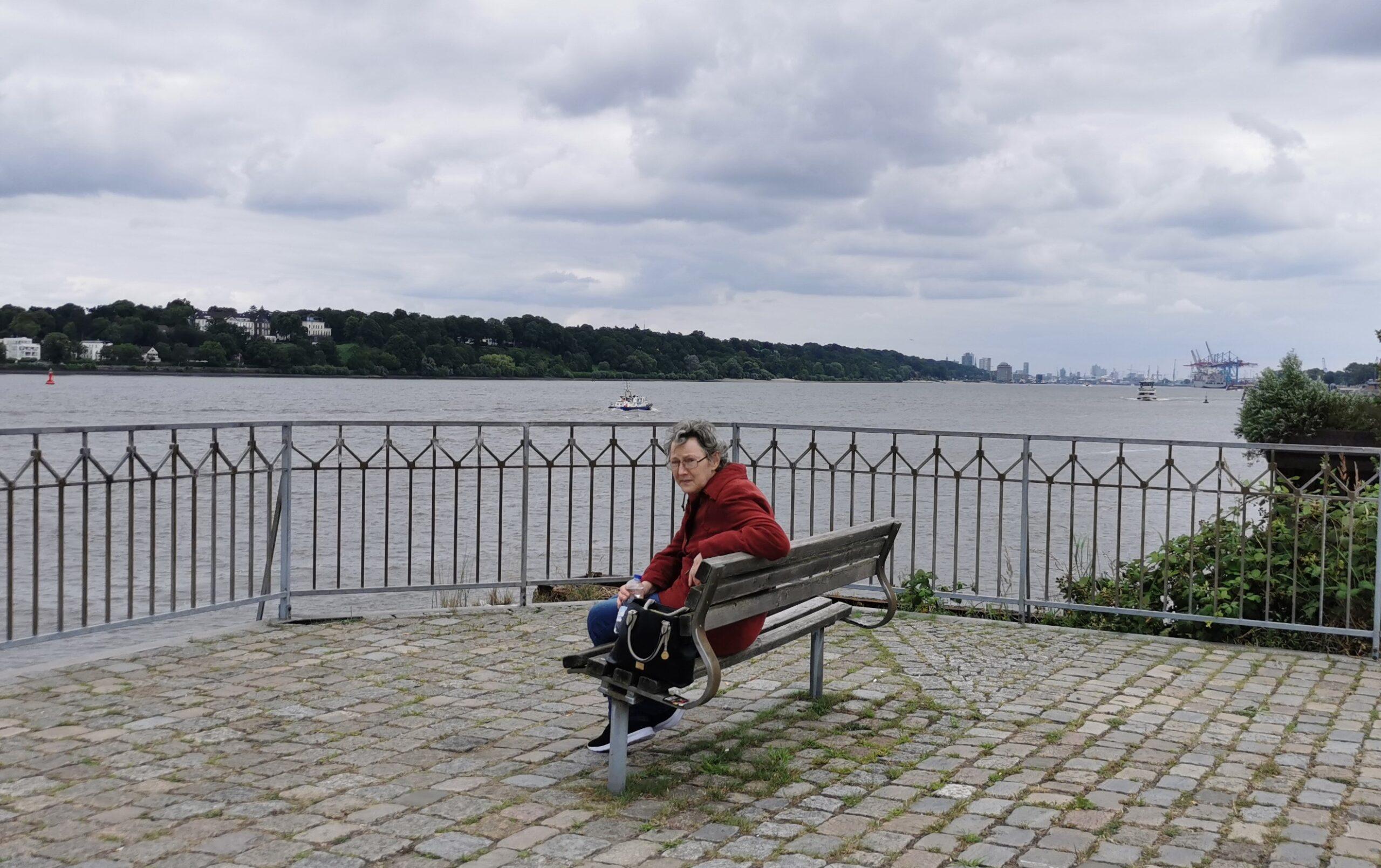 Frau sitzt an der Elbe auf einer Bank, im Hintergrund Hafenkräne.