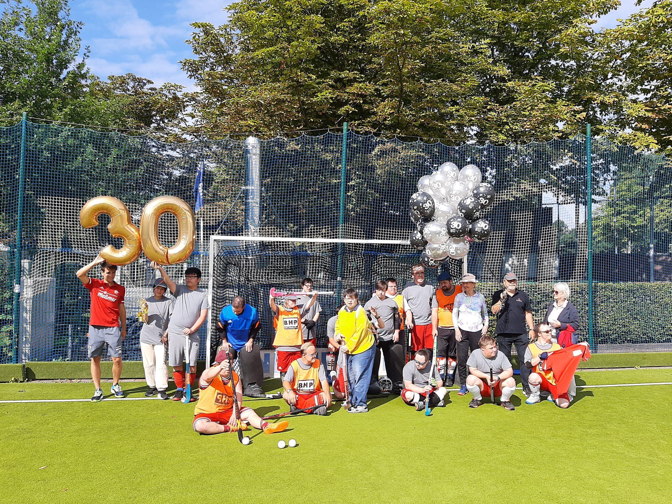 Gruppenfoto der Hockeymannschaft, 30 aus Luftballons und ein Strauß Luftballons