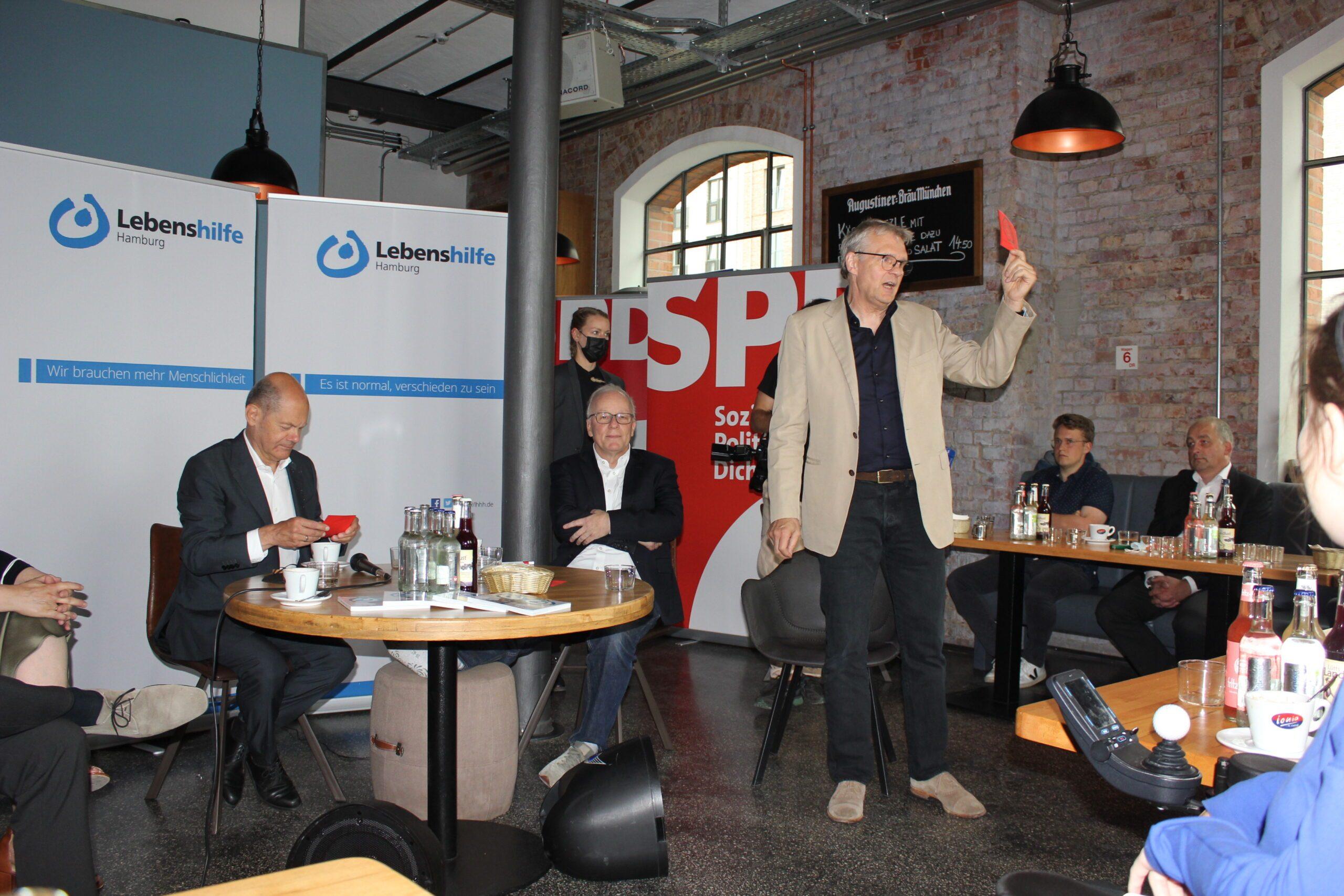 Olaf Scholz und Matthias Bartke sitzen am Tisch. Axel Graßmann steht daneben und hält eine rote Karte hoch.
