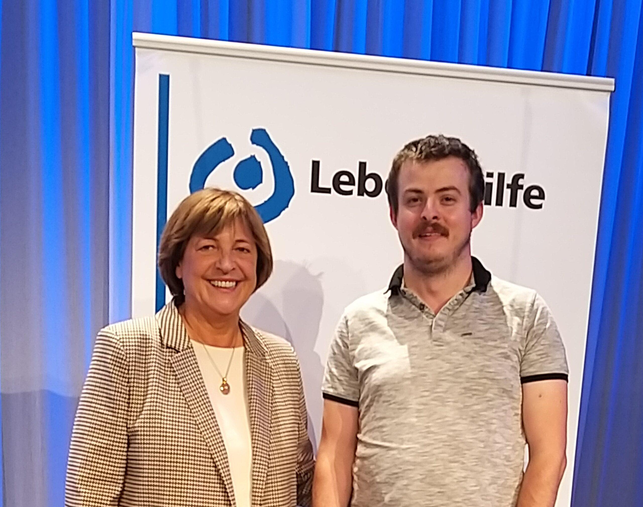 Ulla Schmidt und Alexander Wrusch stehen vor dem Lebenshilfe Logo.